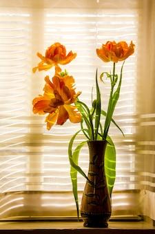 Um buquê de tulipas amarelas laranja em um vaso no parapeito da janela contra a parede de uma janela com uma cortina branca