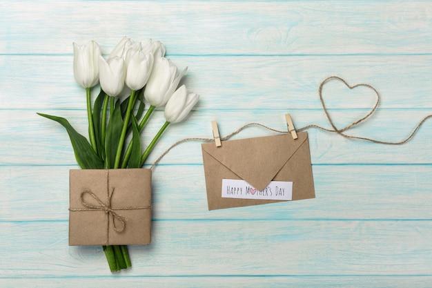Um buquê de tulipas brancas com uma nota de amor e envelope em uma corda em forma de coração e tábuas de madeira azuis. dia das mães Foto Premium