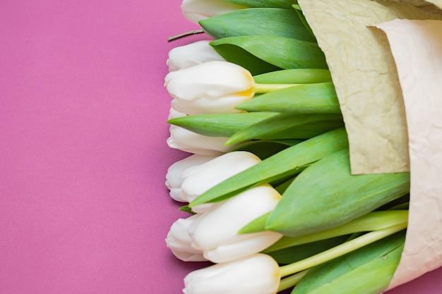 Um buquê de tulipas brancas e um coração de veludo vermelho em uma mesa rosa - o conceito de dia dos namorados.