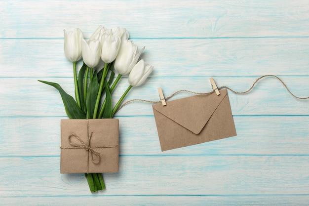 Um buquê de tulipas brancas, xícara de café com uma nota de amor e envelope em tábuas de madeira azuis. dia das mães