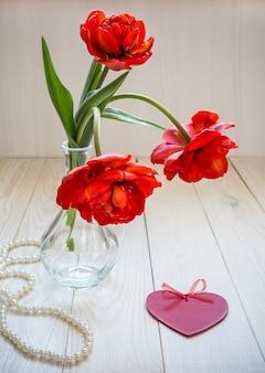 Um buquê de tulipas brilhantes com coração e pérolas