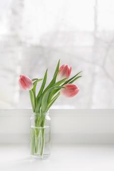 Um buquê de tulipas cor de rosa em uma jarra de vidro está no parapeito da janela da casa.