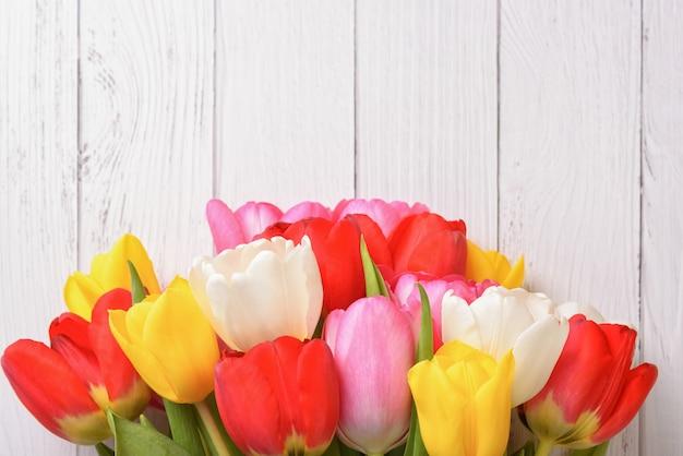 Um buquê de tulipas frescas, brilhantes e multicoloridas em placas de madeira brancas.
