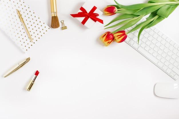 Um buquê de tulipas, um presente com um laço vermelho, um teclado e mouse, cosméticos e um caderno com uma caneta. falt lay blogger com espaço de cópia