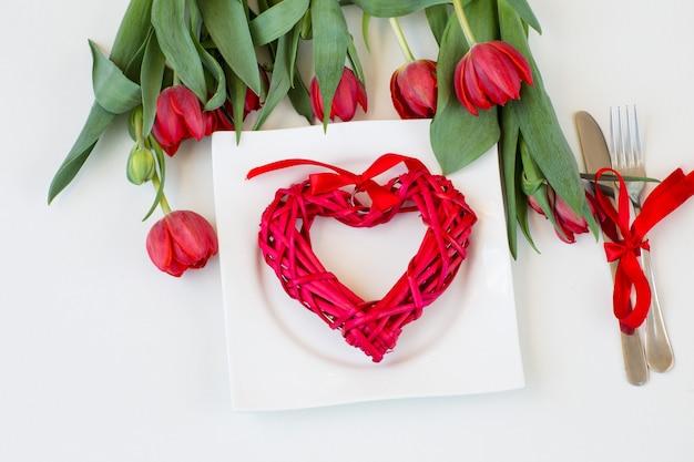 Um buquê de tulipas vermelhas e um coração vermelho de vime em um prato branco, perto de talheres (faca e garfo)