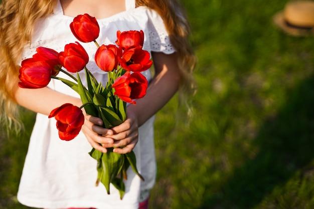 Um buquê de tulipas vermelhas nas mãos da garota com espaço de cópia para grama verde de fundo de texto. foto de alta qualidade