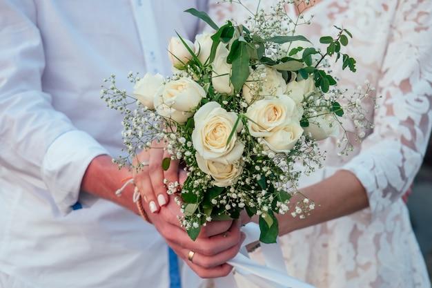 Um buquê de uma noiva de rosas brancas nas mãos dos noivos