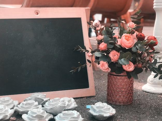 Um buquê em estilo rústico com um quadro e uma placa preta para desenhar um lugar para texto