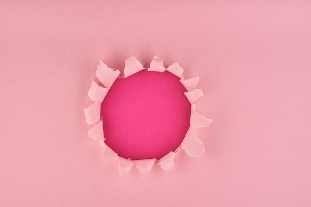 Um buraco rasgado no plano de fundo texturizado rosa, conceito de papel quebrado