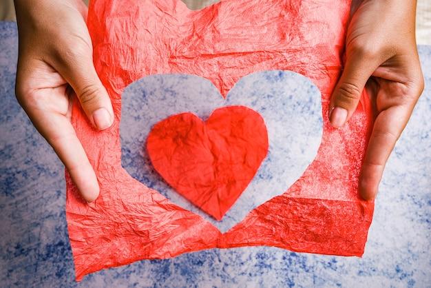 Um buraco vermelho em forma de coração rasgado em um papel nas mãos de uma mulher, isolado em um fundo azul