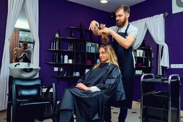 Um cabeleireiro masculino corta o cabelo de uma mulher no salão de beleza de cabelo.