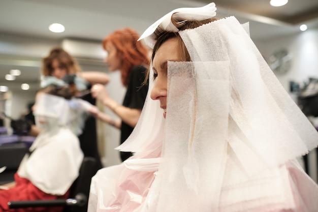 Um cabeleireiro no salão de beleza com clientes