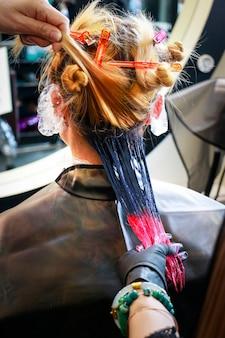 Um cabeleireiro profissional está pintando uma cor vermelha na ponta do cabelo e outra cor escura na raiz