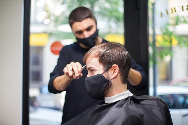 Um cabeleireiro profissional usando máscara protetora cortando o cabelo de uma cliente durante o coronavírus