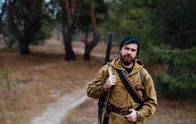 Um caçador barbudo com um chapéu quente e jaqueta cáqui com uma arma e cartuchos segura sua mão em um cinto de couro em um fundo de floresta
