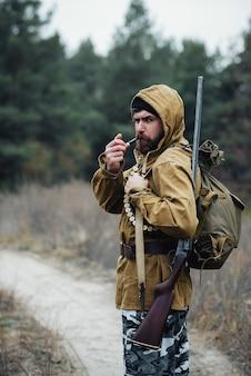 Um caçador barbudo e brutal com chapéu preto, capuz e jaqueta cáqui com uma arma no ombro e cartuchos no peito, fuma um cachimbo e caminha para a floresta