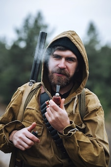 Um caçador barbudo e brutal com chapéu preto, capuz e jaqueta cáqui com uma arma no ombro e cartuchos no peito, fuma um cachimbo e segura um isqueiro