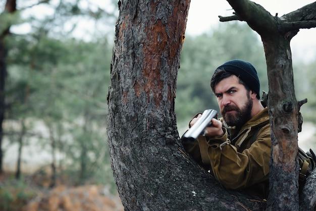 Um caçador brutal de barbudo com um chapéu quente e uma jaqueta cáqui com uma arma de cano duplo olha por trás de uma árvore e mira na presa