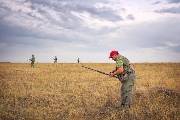 Um caçador carrega munição e outros caçadores se movem pelo campo