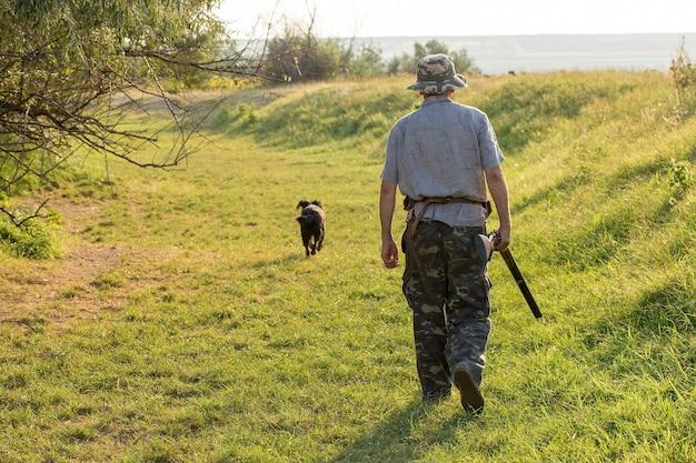 Um caçador com uma arma nas mãos em roupas de caça na floresta de outono em busca de um troféu