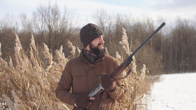 Um caçador experiente está sentado em uma emboscada na caça nos arbustos e procurando presas