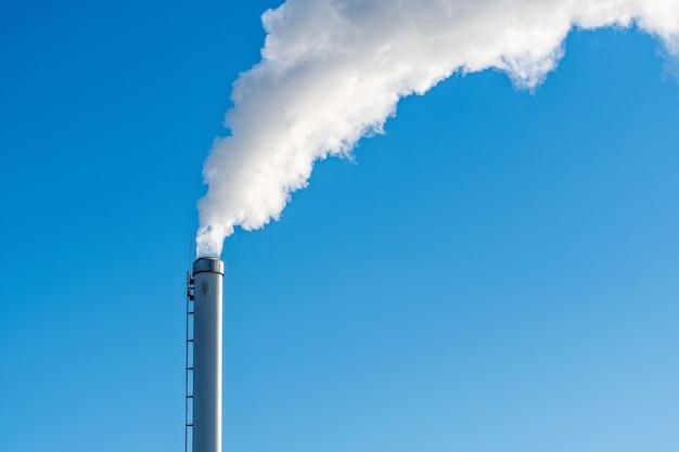 Um cachimbo de fumaça industrial da chaminé em um céu azul nublado, fumaça branca emana do cachimbo