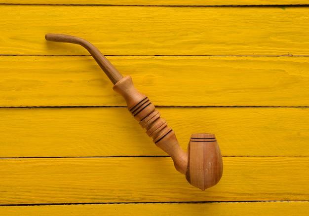 Um cachimbo sobre uma mesa de madeira amarela. vista do topo.
