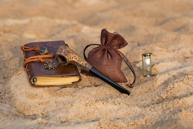 Um cachimbo, um saco de tabaco, uma ampulheta e um livro para entradas