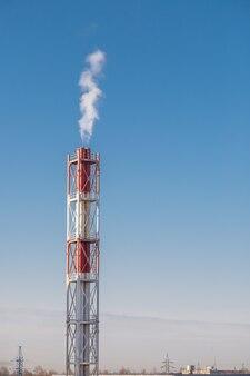 Um cachimbo vermelho e branco lança fumaça branca verticalmente em um clima claro e calmo com céu azul