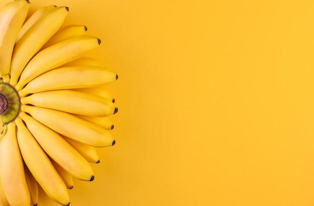 Um cacho de bananas maduras pequenas em um espaço de cópia de fundo amarelo