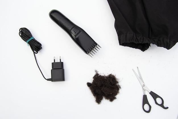 Um cacho de cabelo preto cortado, uma máquina de corte de cabelo tesoura uma capa preta sobre um fundo branco