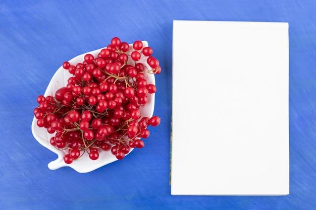 Um cacho de groselha em um prato ornamentado ao lado de um caderno na superfície azul