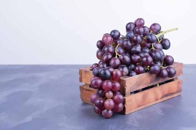 Um cacho de uva em uma bandeja de madeira