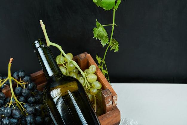 Um cacho de uvas e uma garrafa de vinho em uma mesa branca. foto de alta qualidade