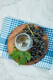 Um cacho de uvas pretas com folhas e uma taça de vinho na superfície branca com uma toalha de mesa azul
