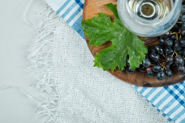 Um cacho de uvas pretas com folhas e uma taça de vinho na superfície branca