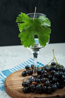 Um cacho de uvas pretas e um copo de vinho com folhas na mesa branca