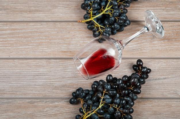 Um cacho de uvas pretas e um copo de vinho no fundo de madeira. foto de alta qualidade