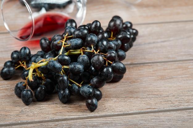 Um cacho de uvas pretas e uma taça de vinho na superfície de madeira