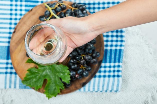 Um cacho de uvas pretas em uma placa de madeira com folhas enquanto a mão segurando um copo vazio