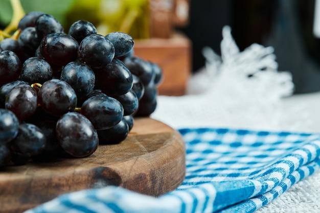 Um cacho de uvas pretas em uma placa de madeira com uma toalha de mesa azul