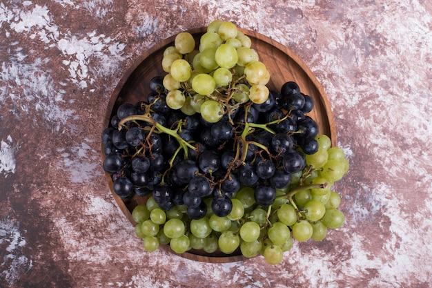 Um cacho de uvas verdes e vermelhas em uma bandeja de madeira