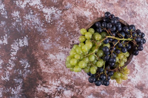Um cacho de uvas verdes e vermelhas no mármore
