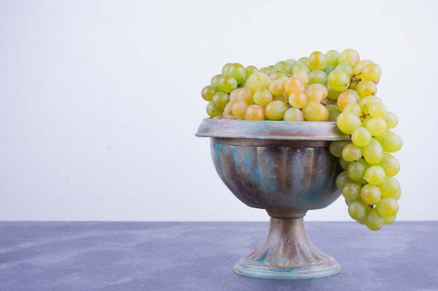 Um cacho de uvas verdes em uma xícara metálica