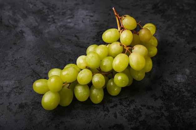 Um cacho de uvas verdes encontra-se em mármore