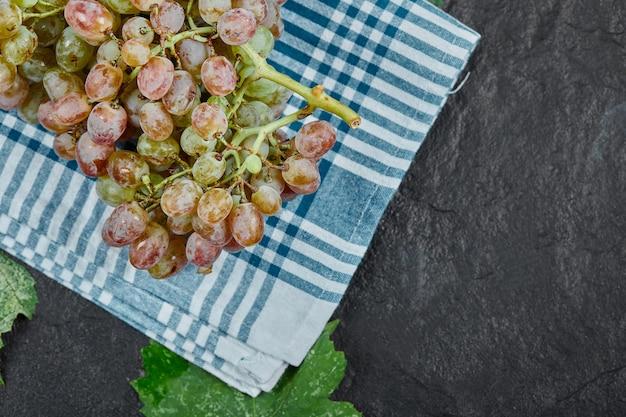 Um cacho de uvas vermelhas com folhas e toalha de mesa azul em fundo escuro. foto de alta qualidade