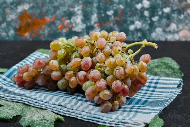 Um cacho de uvas vermelhas com folhas e toalha de mesa azul na mesa escura