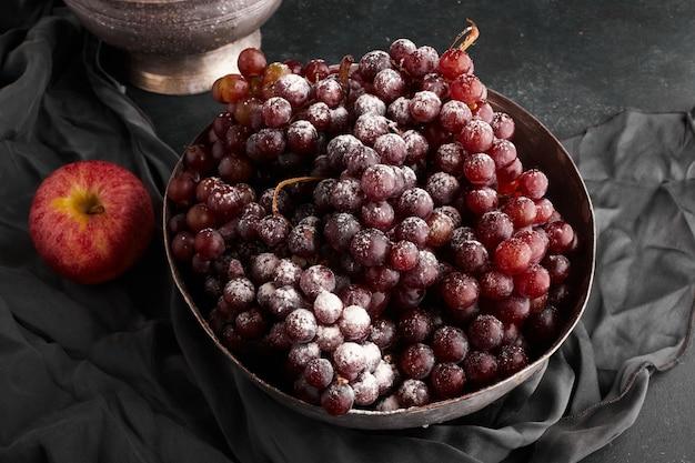 Um cacho de uvas vermelhas em uma tigela metálica, vista superior.