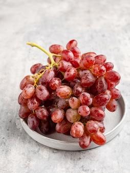 Um cacho de uvas vermelhas maduras com as gotas de água na placa de cerâmica cinza