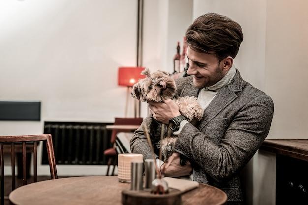 Um cachorro engraçado. o homem está abraçando um cachorro enquanto ele mostra a língua